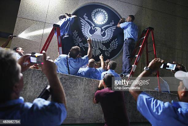 S Embassy employees hang the seal of the United States on the outside of the building a few hours before the ceremonial flagraising August 14 2015 in...