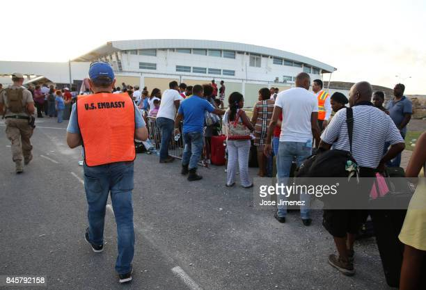 Embassy personal assist US citizens aboard Puerto Rico National Guard C130 plane during evacuation procedures at Princess Juliana Airport on...