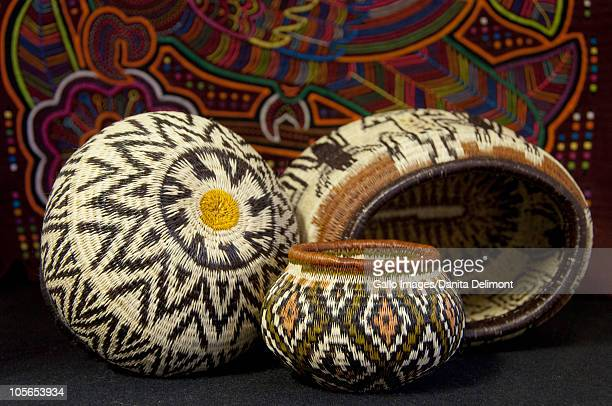 embera indian grass basket in front of colorful hand stitched kuna indian mola - mola kuna fotografías e imágenes de stock