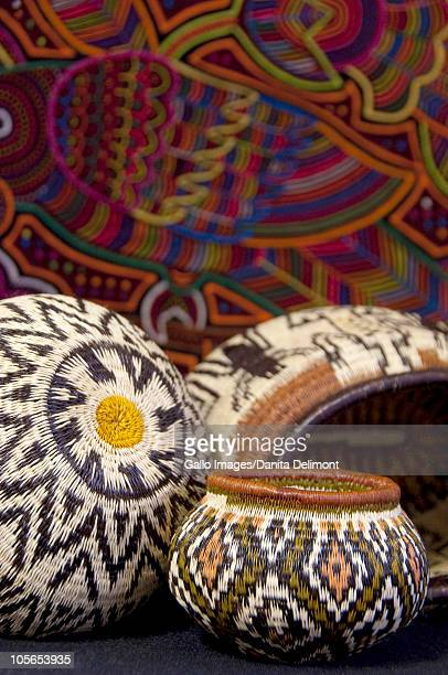 Embera Indian grass basket in front of colorful hand stitched Kuna Indian mola