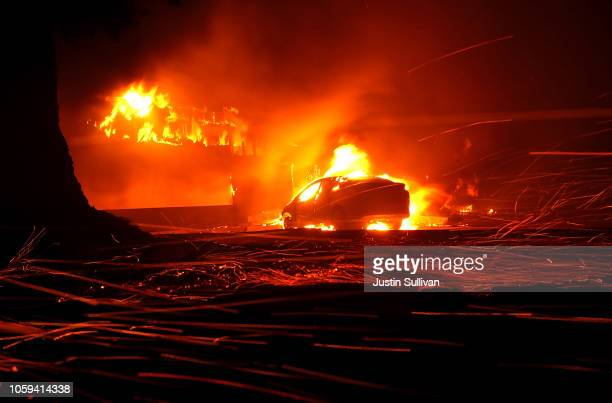 Embers blow in the wind as a Camp Fire burns a KFC restaurant on November 8 2018 in Paradise California Fueled by high winds and low humidity the...