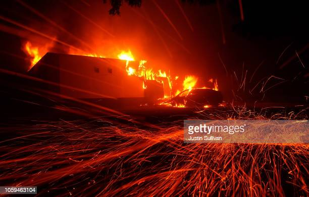 Embers blow in the wind as the Camp Fire burns a KFC restaurant on November 8 2018 in Paradise California Fueled by high winds and low humidity the...