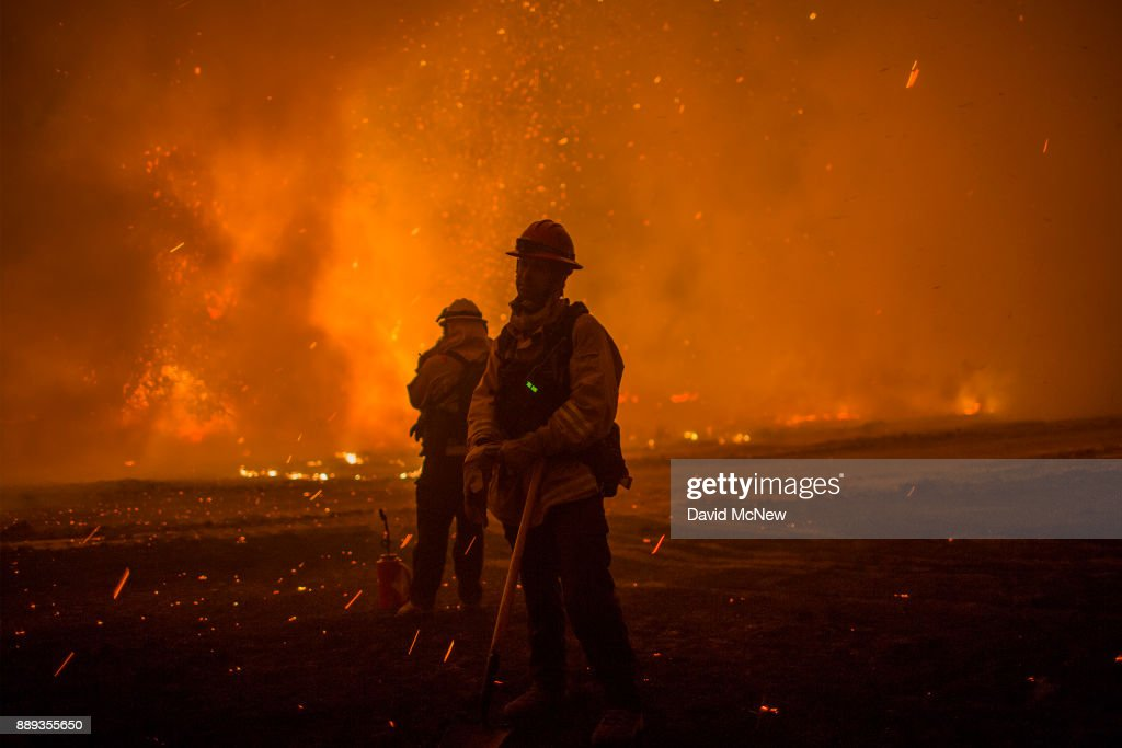 Embers fall on firefighters setting a backfire at night to make progress against the Thomas Fire before the winds return with the daylight near Lake Casitas on December 9, 2017 near Ojai, California. Strong Santa Ana winds have been feeding major wildfires all week, destroying hundreds of houses and forcing tens of thousands of people to stay away from their homes.