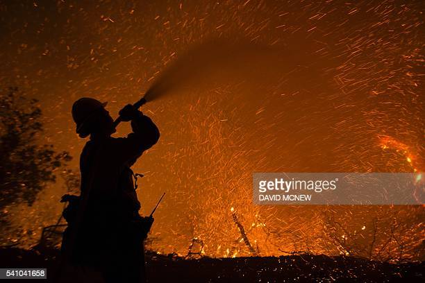 Embers fly around a firefighter with a hose June 17 2016 at the Sherpa Fire near Santa BarbaraCalifornia A fire in the Los Padres National Forest had...