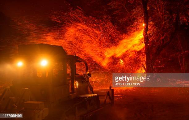 Embers fly off a tree as a bulldozer is prepared to help fight fire during the Kincade fire near Geyserville California on October 24 2019 fastmoving...