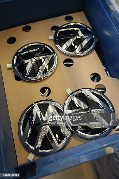 VW emblems lie in a box at the assembly line for Volkswagen Touran and Tiguan cars at the Volkswagen factory on March 7 2012 in Wolfsburg Germany In...