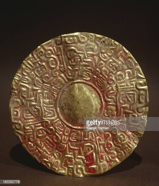 Embossed gold disc, possibly earring or pendant to be suspended from a garment or headdress, Peru. Mochica. 100 600 AD. North coast of Peru.