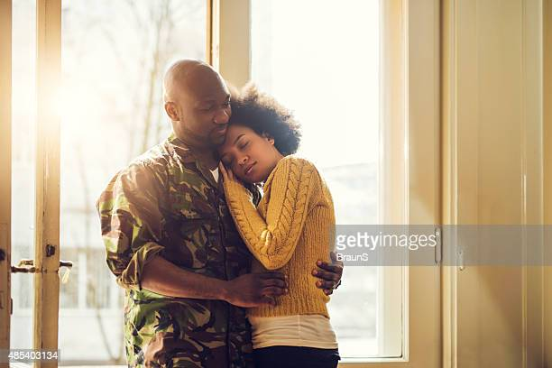 embraced african american soldier and his wife at the door. - military spouse stock pictures, royalty-free photos & images