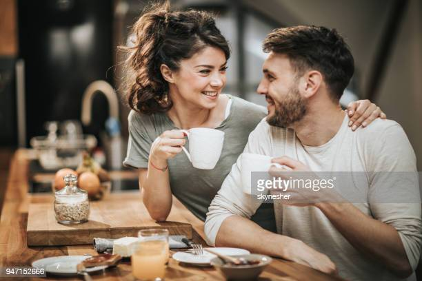 embraced couple in love communicating during coffee time in the kitchen. - coffee drink stock pictures, royalty-free photos & images