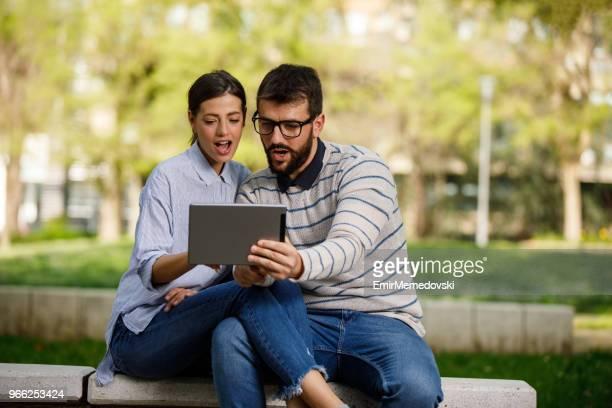 Umarmt paar mit digital-Tablette auf der Bank sitzen