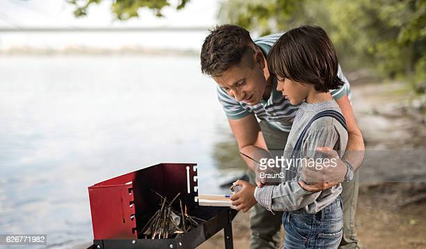 Embraced father and son preparing firewood for barbecue.