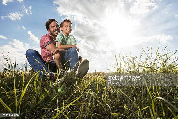 Embraced father and son relaxing together in a meadow.