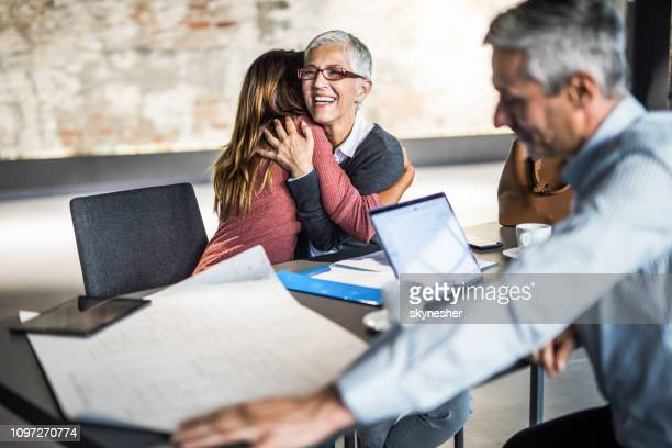 embraced mother and daughter on a meeting with real estate agent. - affettuoso foto e immagini stock
