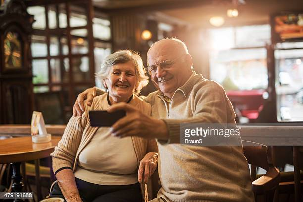 Embraced old couple taking a selfie with cell phone.