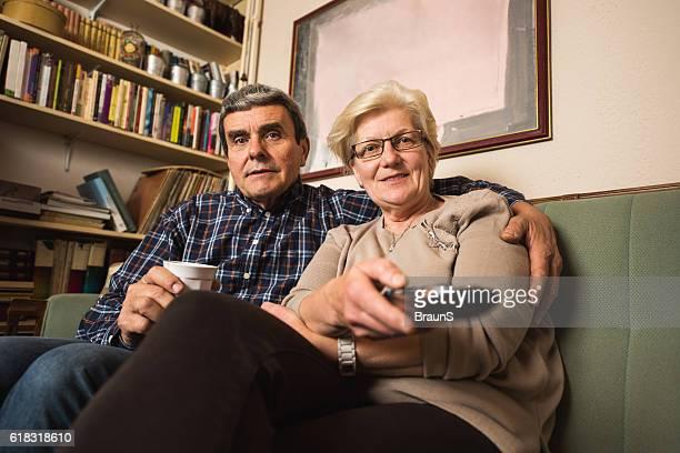 Embraced senior couple enjoying at home while watching TV.