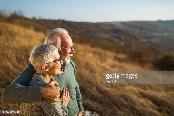embraced senior couple enjoying in autumn day on a field. - retirement stock pictures, royalty-free photos & images