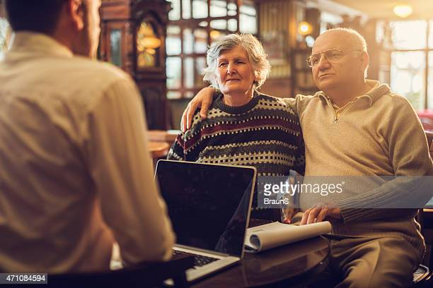 Embraced senior couple having a meeting with insurance agent.
