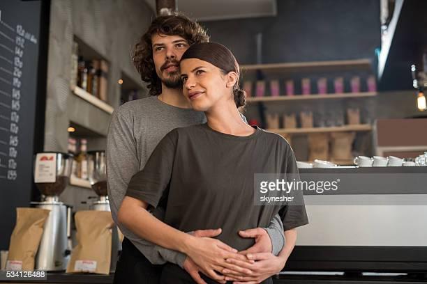 embraced smiling cafe owners standing in a coffee shop. - handen op de buik stockfoto's en -beelden