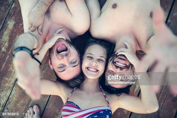 embraced smiling friends lying on wooden pier and taking selfie - bikini top stock pictures, royalty-free photos & images