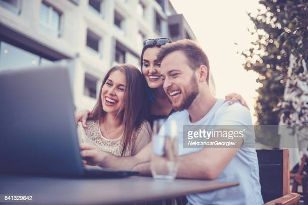 Embraced Smiling Friends on Video Conference Outdoors in Coffee Shop