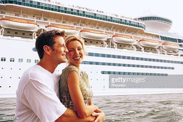 embracing couple in front of cruise ship - kreuzfahrt stock-fotos und bilder