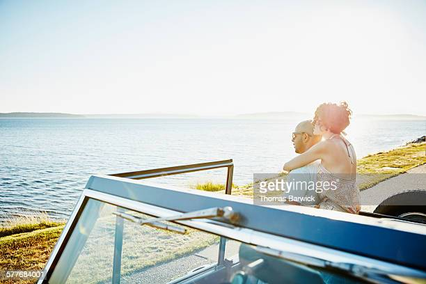 Embracing couple leaning against convertible