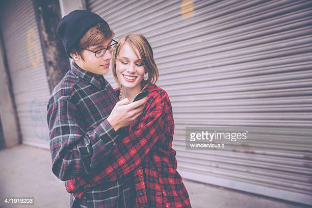 embracing couple looking at cell phone - teenage couple stock photos and pictures