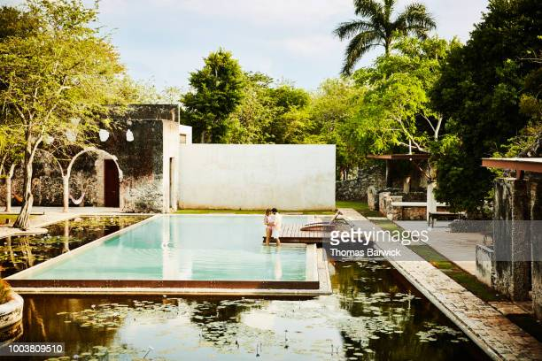 Embracing couple standing at edge of pool in courtyard of luxury tropical resort