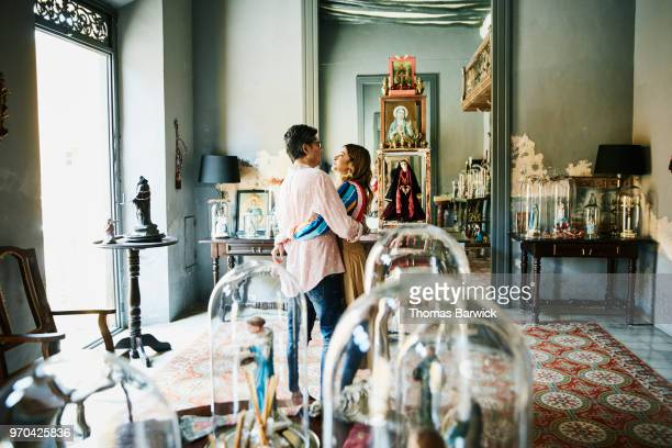 Embracing couple standing in boutique while shopping during vacation