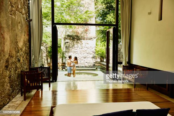 Embracing couple standing in plunge pool outside of room at luxury tropical resort