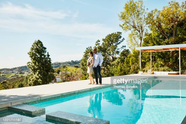 embracing couple standing next to pool and admiring view - sports venue stock pictures, royalty-free photos & images