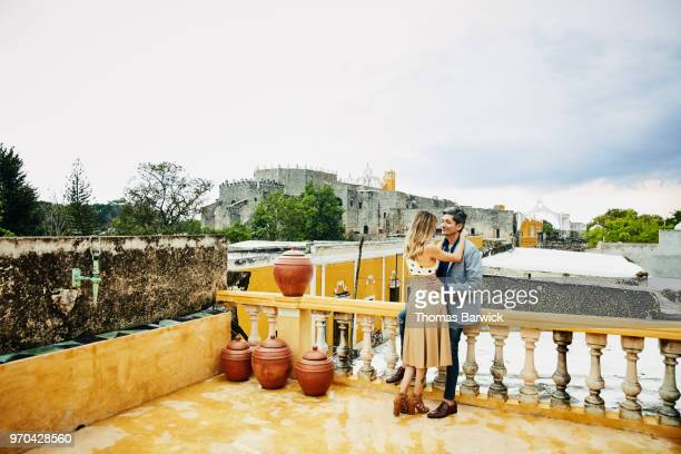 Embracing couple standing on hotel rooftop deck over looking city of Izamal