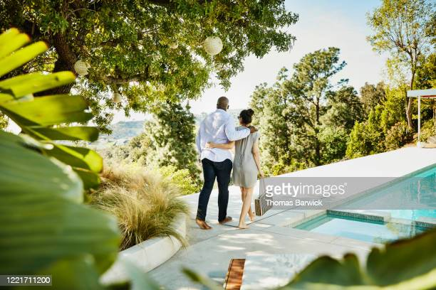 embracing couple walking on pool deck - black hair stock pictures, royalty-free photos & images
