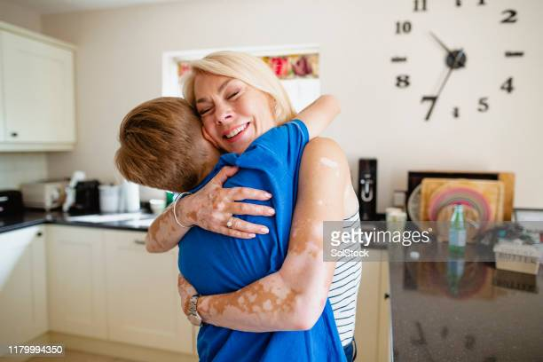 embracing his mother - showus stock pictures, royalty-free photos & images