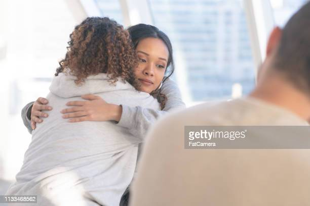embracing in group therapy - addiction stock pictures, royalty-free photos & images