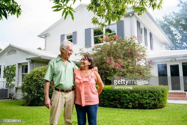 embracing latin american seniors in backyard of miami home - florida landscaping stock pictures, royalty-free photos & images
