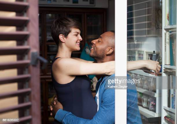 Embracing pregnant couple in kitchen smiling at each other