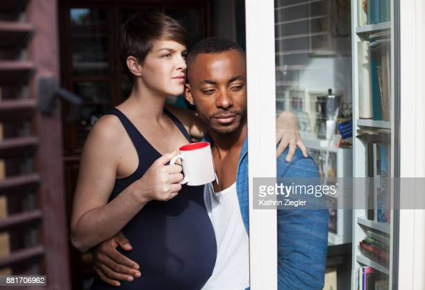 Embracing pregnant couple in kitchen, woman is holding a cup of tea