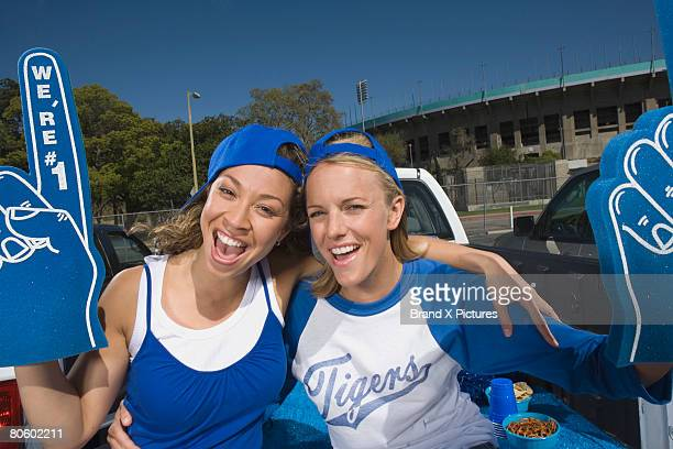 embracing women fans - foam finger stock photos and pictures