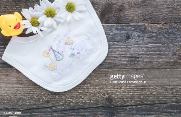 Embroidery baby bib,  three yellow daisies and rubber duck on old wooden background with copy space. Directly above