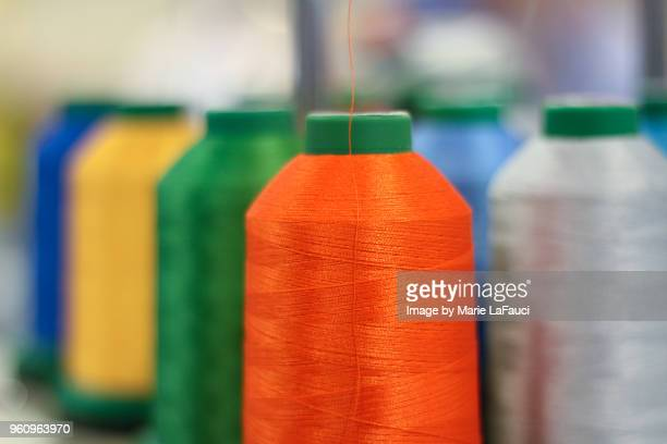 embroidery spool with orange thread - marie lafauci stock pictures, royalty-free photos & images