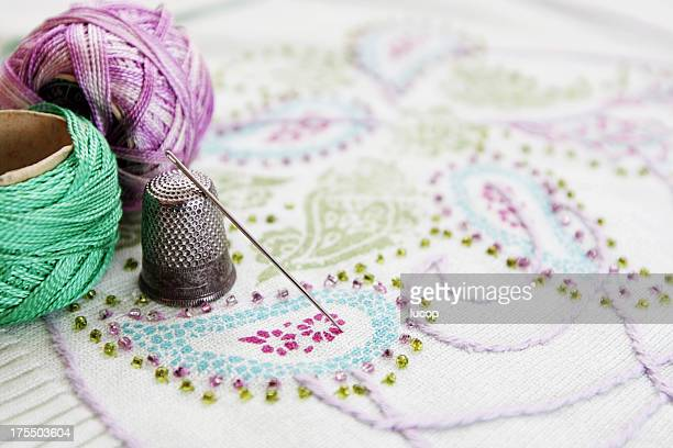 Embroidery thread, needle and thimble on a embroidery.
