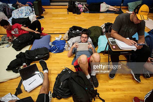 EmbryRiddle Aeronautical University student TJ Rusiniak watches weather updates on his iPad at a public shelter set up at Mainland High School...