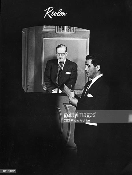 Emcee Hal March reads questions to contestant Gino Prato who stands inside the isolation booth on the darkened set of the TV quiz show 'The $64000...