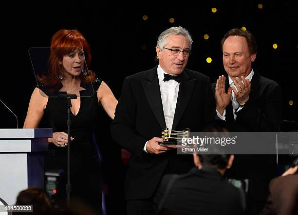 Emcee Reba McEntire and actor Billy Crystal present honoree Robert De Niro with an award onstage during Muhammad Ali's Celebrity Fight Night XX held...