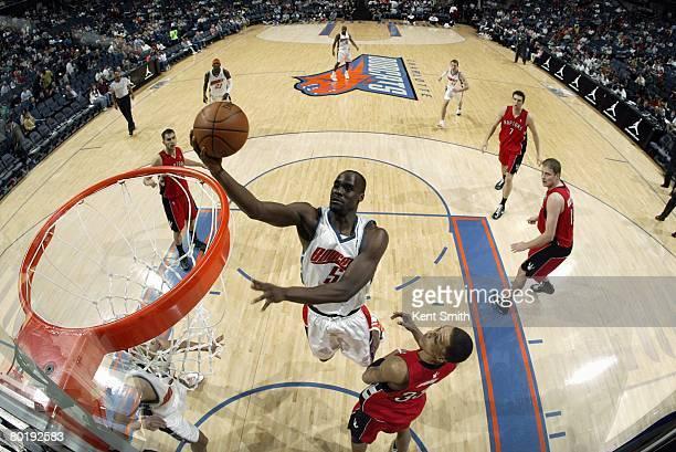 Emeka Okafor of the Charlotte Bobcats shoots a layup against Jamario Moon of the Toronto Raptors during the game at the Charlotte Bobcats Arena on...