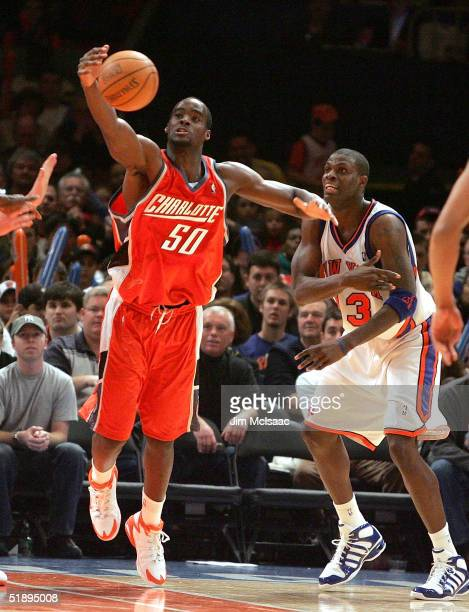 Emeka Okafor of the Charlotte Bobcats tries to control a loose ball against Nazr Mohammed of the New York Knicks during the second half of their game...