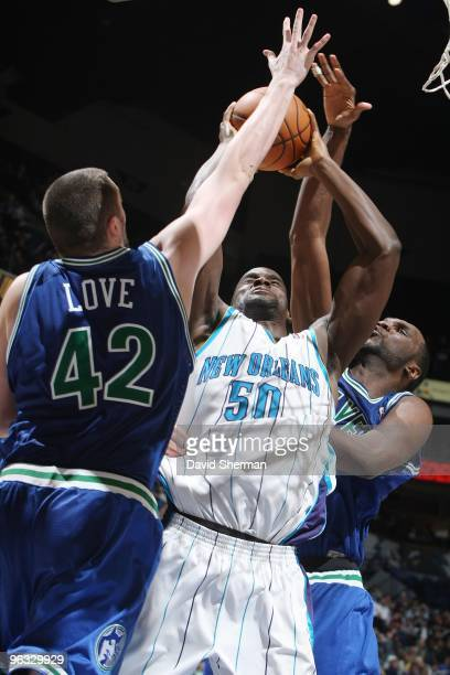 Emeka Okafor of the New Orleans Hornets goes up for a shot against Kevin Love and Al Jefferson of the Minnesota Timberwolves during the game at...