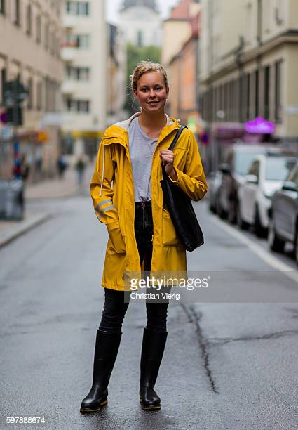 Emelie Resvik wearing a yellow rain coat grey tshirt dark denim jeans black gumboots wellies outside By Malina during the first day of the Stockholm...