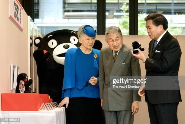 Emeperor Akihito and Empress Michiko listen to Kumamoto Governor Ikuo Kabashima 's explanation on how the prefecture use their bear-like mascot...